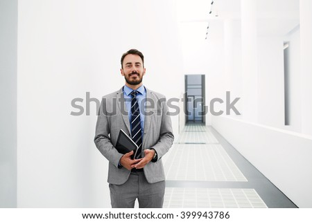 Smiling man employer with digital tablet in hands is posing before meeting with his staff, while is standing in hallway enterprise with copy space for advertising text message or promotional content - stock photo