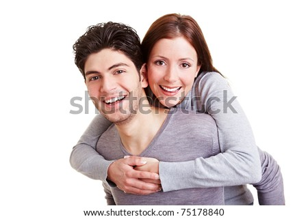Smiling man giving young woman a piggyback ride