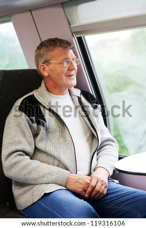 smiling man goes in a train and looks out of the window - stock photo