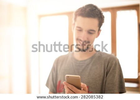 Smiling man hand holding the Gold smartphone, Focus on phone. - stock photo