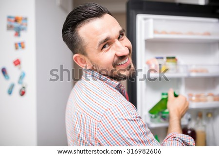 Smiling man holding a beer and standing by the fridge - stock photo