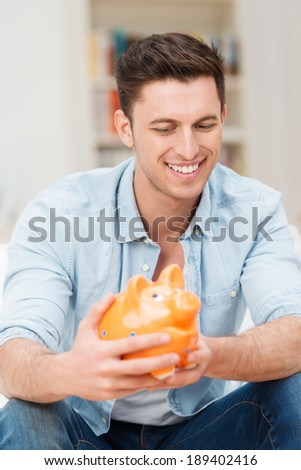 Smiling man holding a piggy bank grinning as he imagines the things he can do with the money he has saved - stock photo