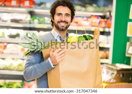 Smiling man holding a shopping bag in a supermarket - stock photo
