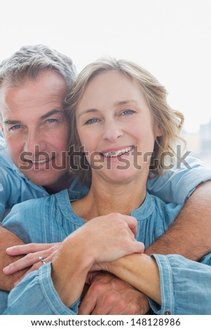 Smiling man hugging his wife from behind at home in the living room