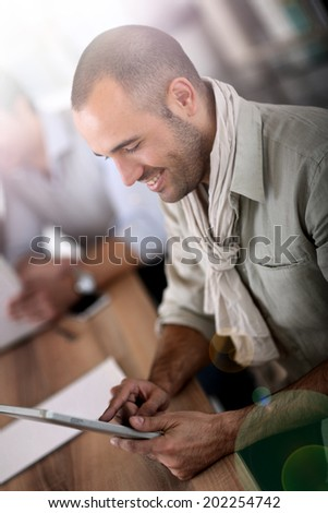 Smiling man in office using digital tablet - stock photo