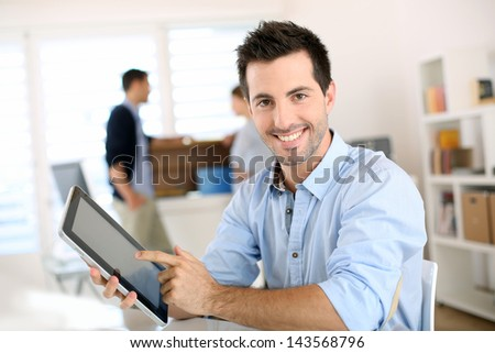 Smiling man in office working on digital tablet - stock photo
