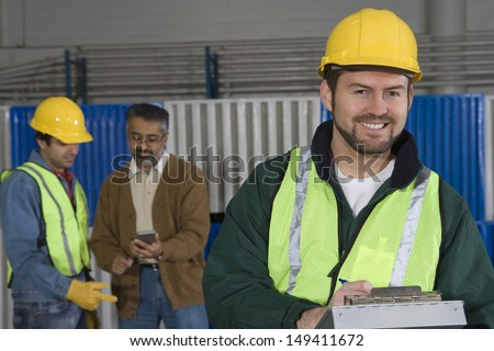 Smiling man in protective wear with colleague in background at factory - stock photo