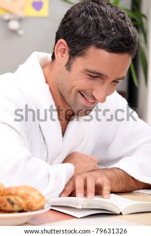 smiling man in robe reading - stock photo