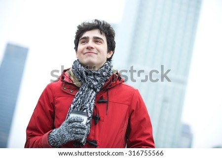 Smiling man in warm clothing looking away while holding disposable cup outdoors - stock photo