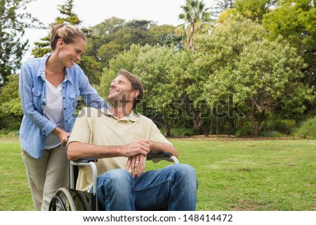 Smiling man in wheelchair talking with partner in the park on sunny day - stock photo