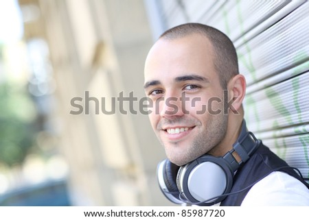Smiling man listening to music in the street - stock photo