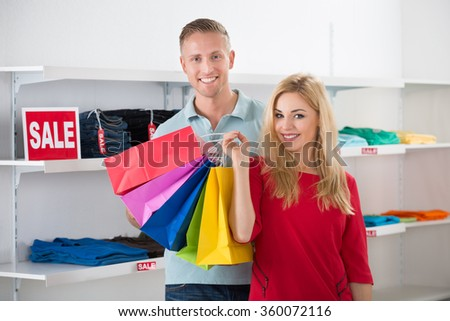 Smiling man looking at woman carrying shopping bags in store