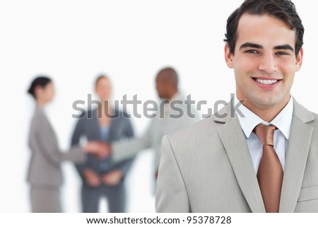 Smiling man of business with trading partners behind him against a white background - stock photo