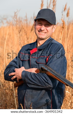 Smiling man on a hunt among autumn grass - stock photo