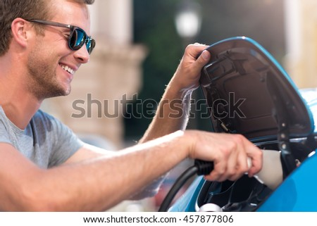 Smiling man plugging cable to electric car