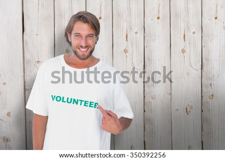 Smiling man pointing to his volunteer tshirt against wooden background