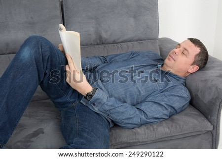 Smiling man reading a book and relaxing on sofa
