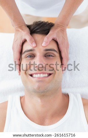 Smiling man receiving head massage in medical office - stock photo