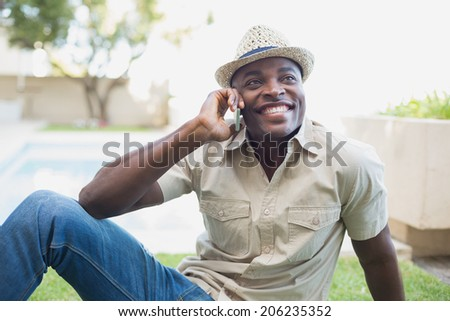 Smiling man relaxing in his garden talking on phone on a sunny day - stock photo