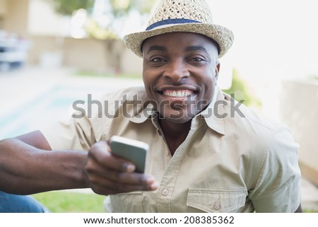 Smiling man relaxing in his garden texting on phone on a sunny day - stock photo
