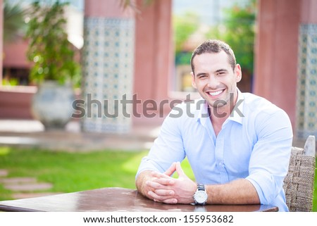 Smiling man seated at a table in a cafe - stock photo