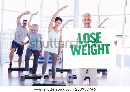 Smiling man showing large poster against lose weight - stock photo