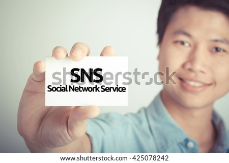 """smiling man showing """" SNS """" on card - stock photo"""