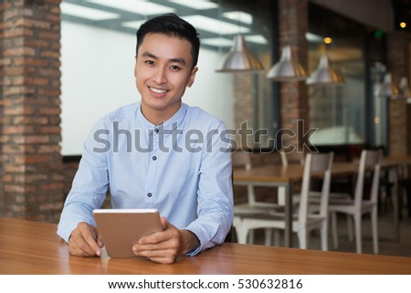 Smiling Man Sitting at Cafe Table with Tablet