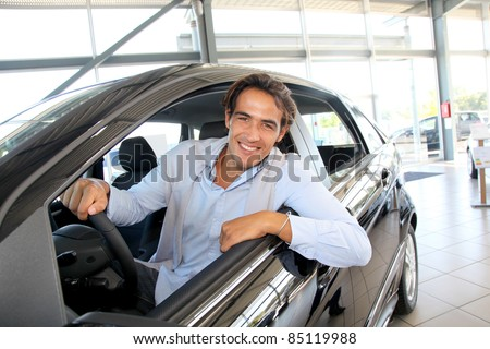 Smiling man sitting at the steering-wheel of brand new car - stock photo