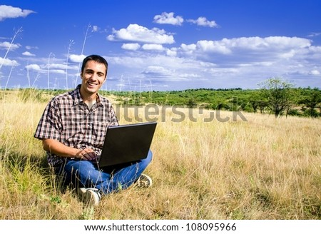 Smiling man sitting in nature with laptop in his lap - stock photo