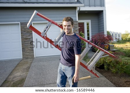 Smiling man standing in front of house holding ladder and hammer. Horizontally framed photo. - stock photo