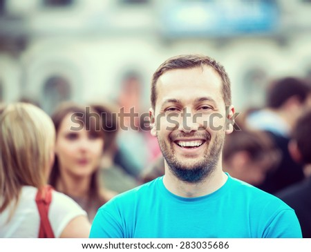 Smiling man standing on a crowded street - stock photo