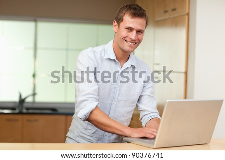 Smiling man surfing the web in the kitchen