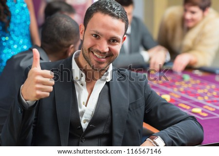 Smiling man thumbs up at the casino at roulette table - stock photo