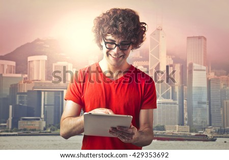 Smiling man using a tablet - stock photo