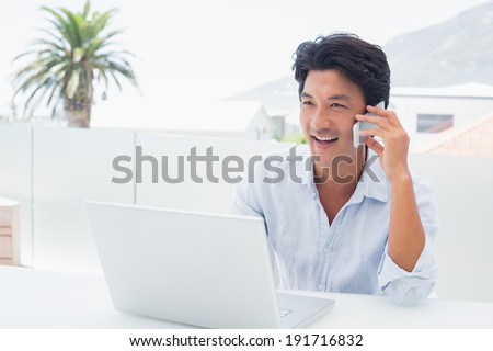 Smiling man using his laptop and talking on phone outside on a balcony - stock photo