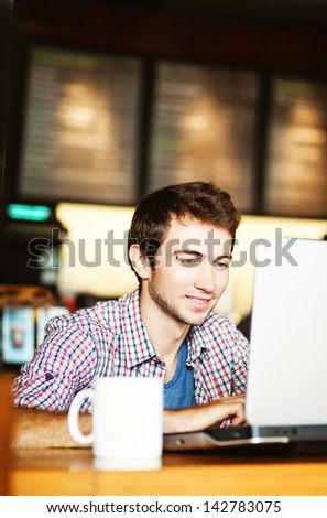 smiling man using laptop in the cafe