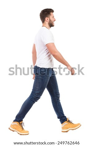 Smiling man walking in jeans and white t-shirt. Full length studio shot isolated on white. - stock photo