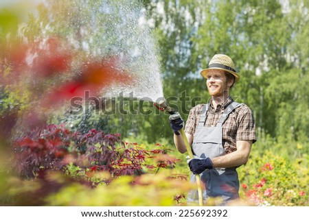 Smiling man watering plants at garden - stock photo