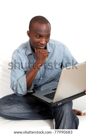 Smiling man websurfing on laptop computer at home - stock photo