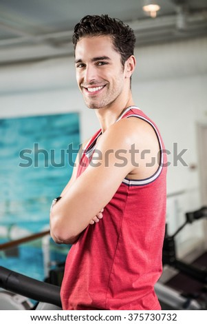 Smiling man with arms crossed in the gym - stock photo