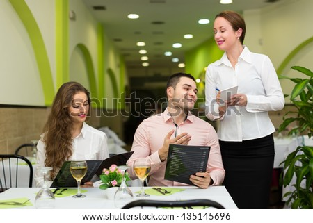 Smiling man with beautiful girlfriend making order in cafe. Focus on man