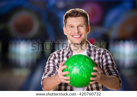 Smiling man with bowling ball - stock photo