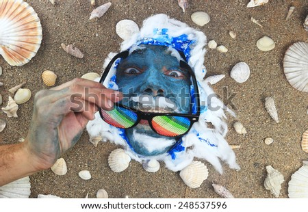 smiling man with colorful sunglasses under a bed of seashells - stock photo