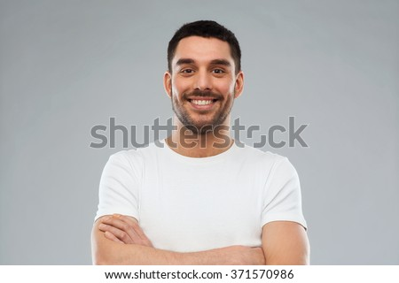 smiling man with crossed arms over gray background - stock photo