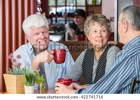 Smiling man with friends in a coffee house - stock photo