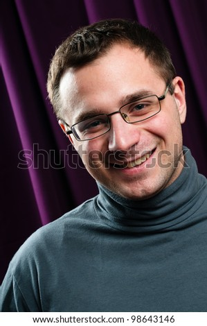 Smiling man with glasses portrait with purple curtain on background