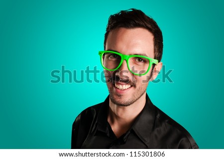 smiling man with green eyeglasses and black jacket on blue background