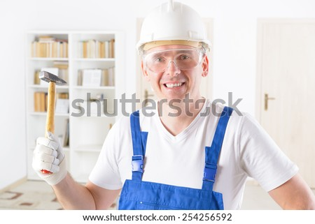 Smiling man with hammer wearing protective helmet and glasses