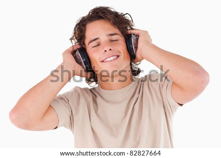 Smiling man with headphones having eyes closed in a studio